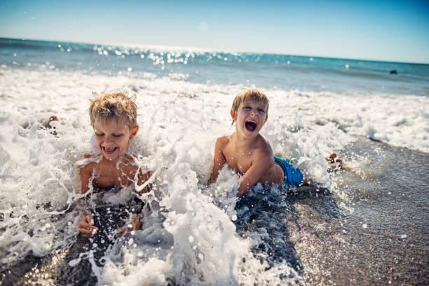 jongetjes spatten in de golven van de zee in toscane - strandvakantie stockfoto's en -beelden
