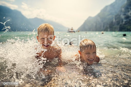 istock Little boys splashing in the waves of Garda Lake, Italy 1062137456