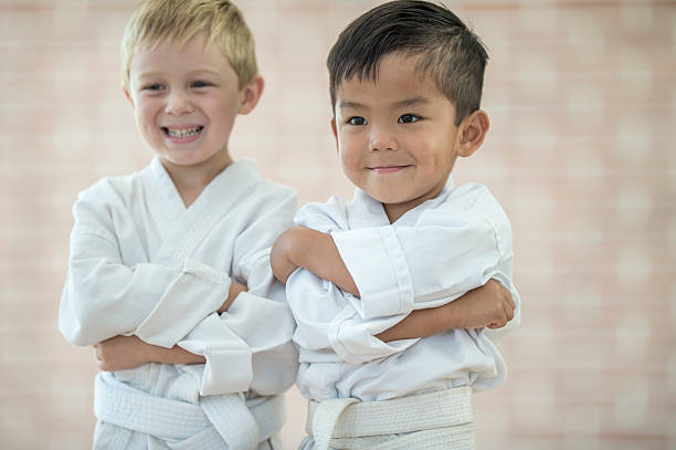 little boys taking a karate class - artes marciales fotografías e imágenes de stock