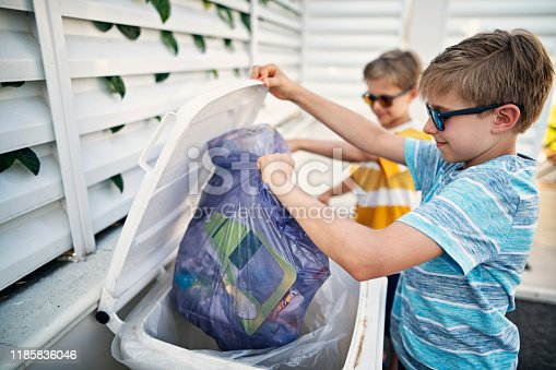 Boys taking out the segregated garbage. The boys are throwing paper waste to garbage bin. Nikon D850