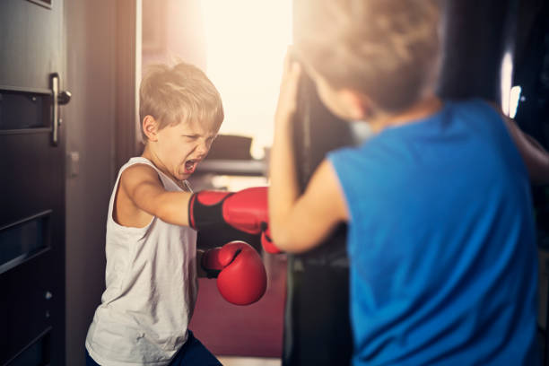 Little boys training boxing with punching bag stock photo