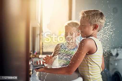 Little boys aged 8 are washing hands in a bathroom. Boys are making a lot of mess - playing and splashing with water. Nikon D850