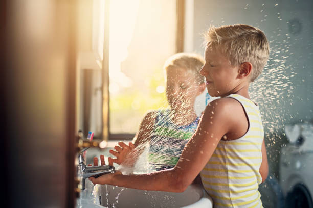 Little boys washing hands and playing with water Little boys aged 8 are washing hands in a bathroom. Boys are making a lot of mess - playing and splashing with water. Nikon D850 mischief stock pictures, royalty-free photos & images