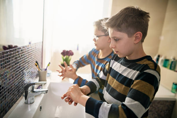 Little boys washing hands thoroughly stock photo