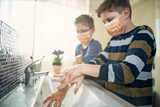 Little boys wearing face masks washing hands thoroughly stock photo