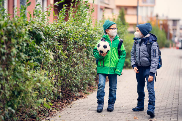Little boys wearing pollution masks going to school Two little boys going to school on cold autumn morning. The boys are wearing pollution masks. Nikon D850 pollution mask stock pictures, royalty-free photos & images