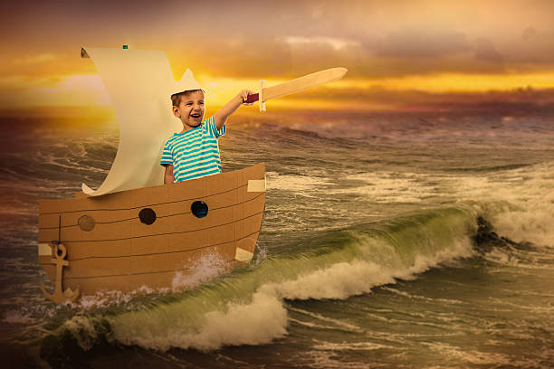 Little brave captain Portrait of a child with a wooden sword. He floats in a cardboard boat on the sea. anchor athlete stock pictures, royalty-free photos & images