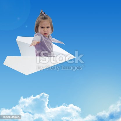 istock little brave girl fly on a paper plane in sky above clouds. Contemporary art collage. dream like 1098349620
