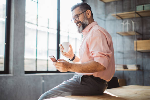 Little break with my phone Mature businessman working at modern office space. Sitting at the table, using phone . Holding cup of coffee. only mature men stock pictures, royalty-free photos & images
