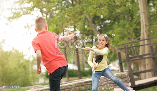 618034312 istock photo Little brother and sister blowing bubbles outdoor 1211217362
