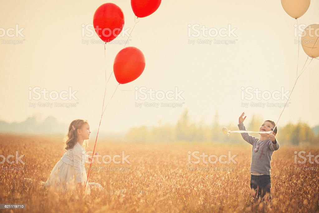 Little brother and sister plating with balloons stock photo