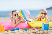 Little girl with pigtails and a little blond boy with short hair,wearing dark sun glasses, spend time together on the sandy beach,lie side by side on air mattresses for swimming on the blue ocean,mattresses yellow and pink