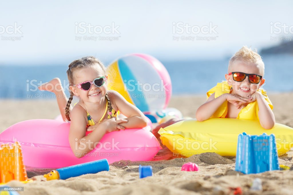 Little brother and sister playing together on sandy beach stock photo
