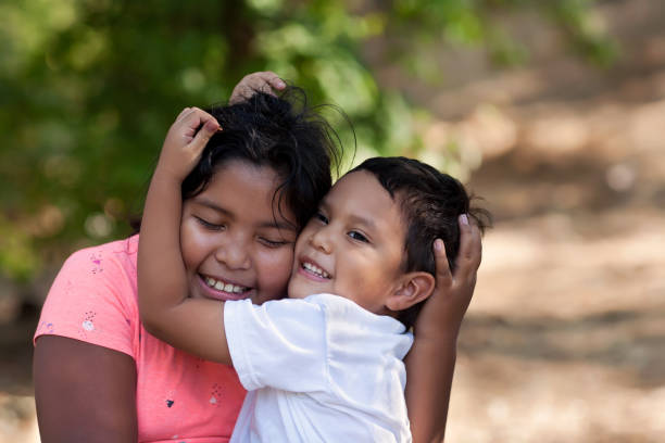 Little brother is hugging his older sister with his arms around her face and both are smiling in outdoor setting. stock photo