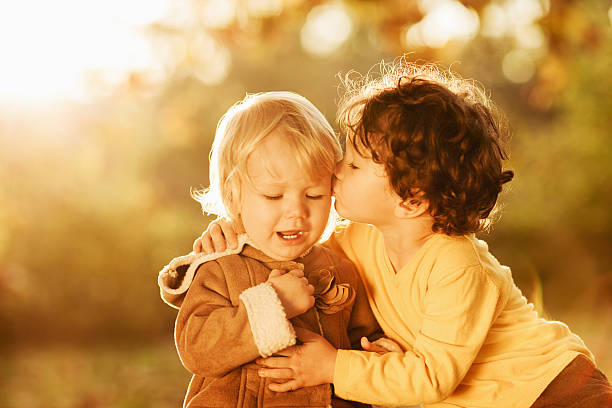 little brother kissing his sister - little girls little boys kissing love stock photos and pictures