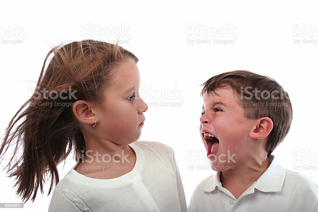 Little brother screaming at her older sister. stock photo