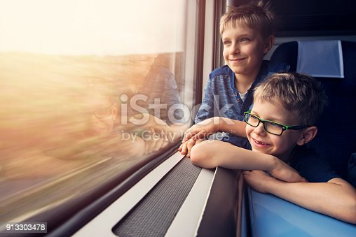 Little boy enjoying train journey. Tired little boy is listening to the music and looking out of the window.