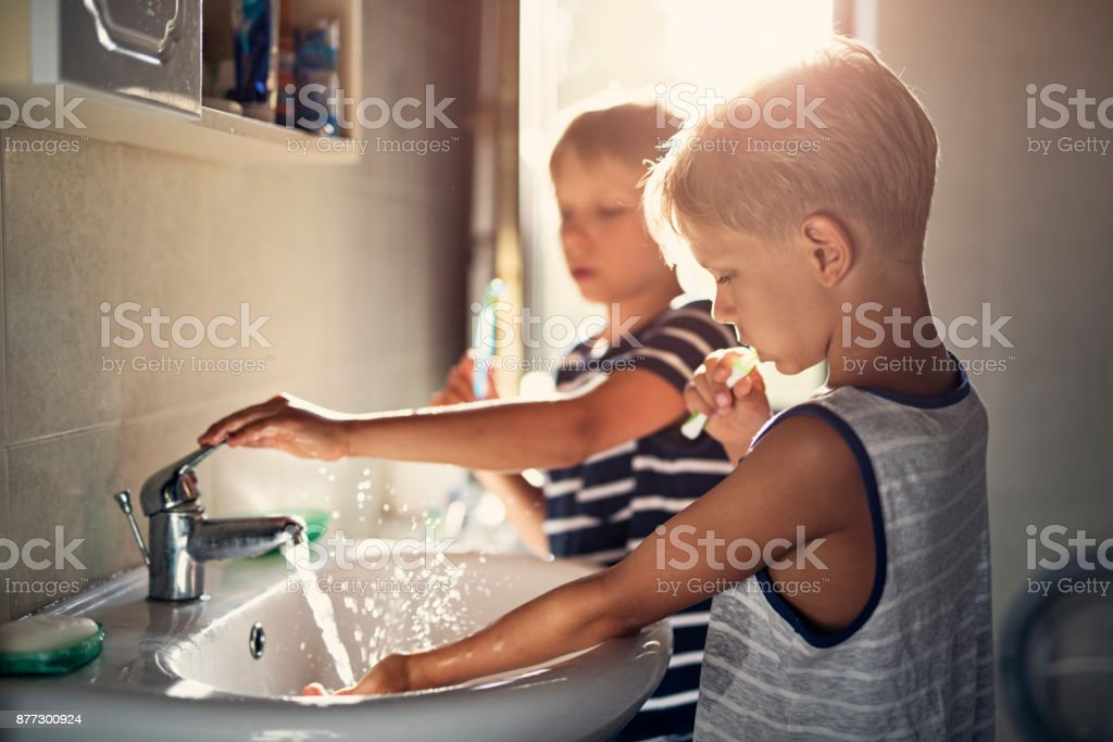 Little brothers brushing teeth stock photo