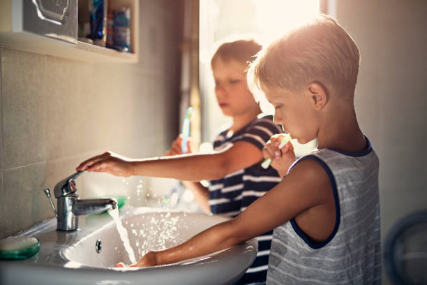 kleine brüder zähneputzen - kinder wc stock-fotos und bilder
