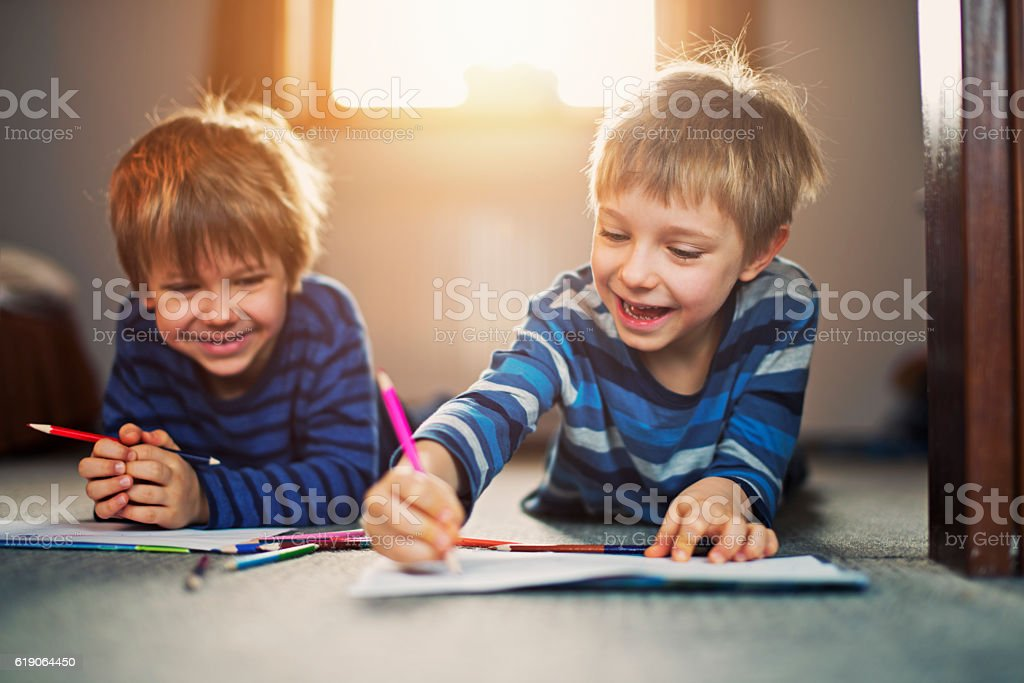 Little brothers enjoying drawing on the floor Two happy little boys aged 5 drawing on the floor. Sun is backlighting the kids from the window behind them with warm light. 4-5 Years Stock Photo