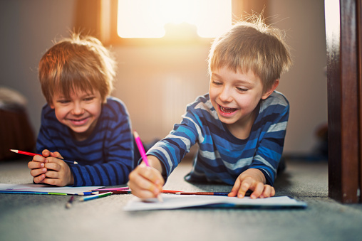Little Brothers Enjoying Drawing On The Floor Stock Photo - Download Image Now