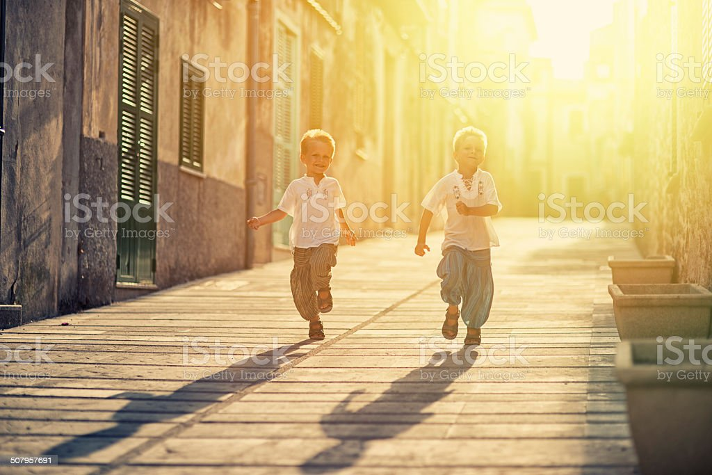 Little brothers running down a  mediterranean street stock photo