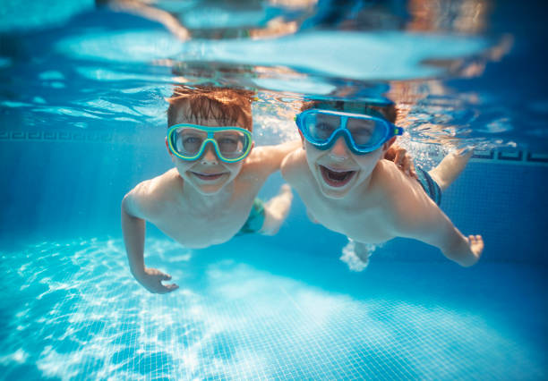 Little brothers swinning underwater together stock photo