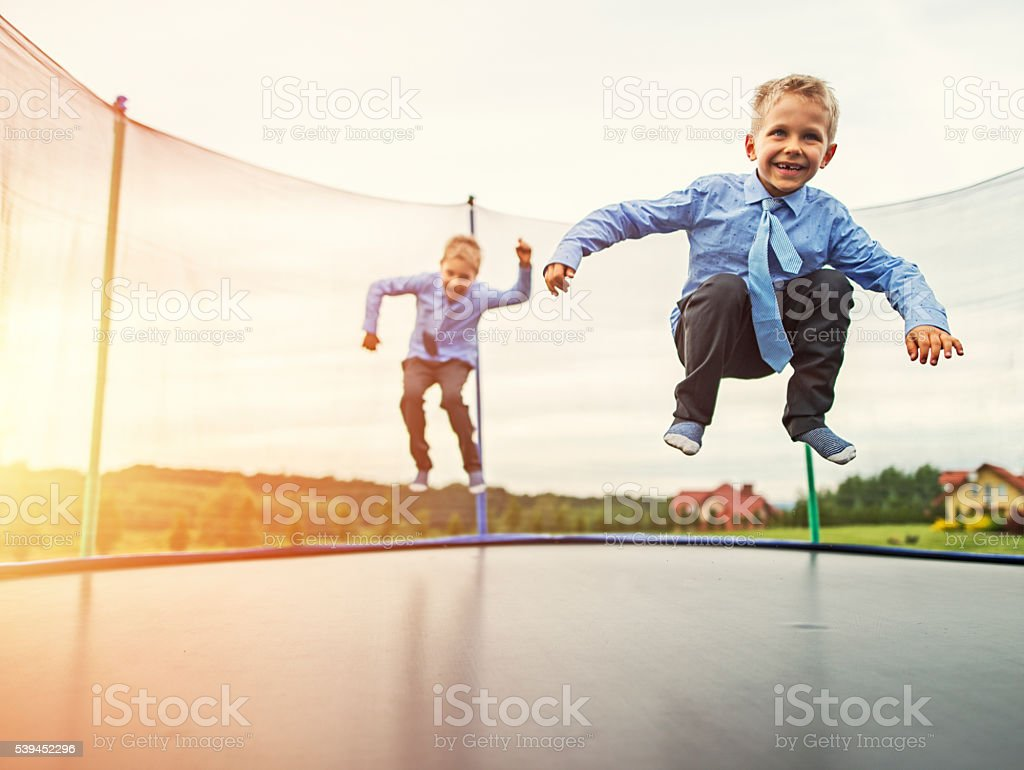 Little brothers wearing suits jumping on trampoline stock photo