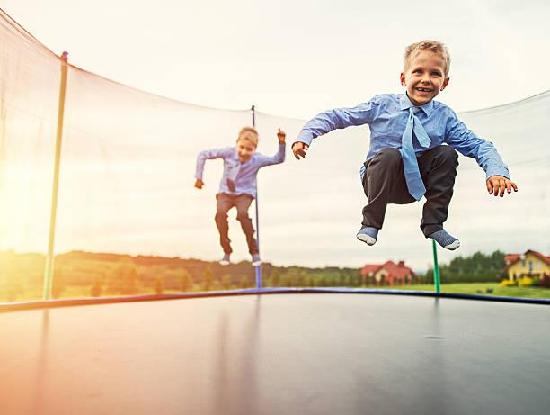 pequeños hermanos el uso de trajes de salto sobre trampolín - trampolín artículos deportivos fotografías e imágenes de stock