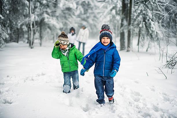 little brothers with family enjoying winter walk in forest. - schneespiele stock-fotos und bilder
