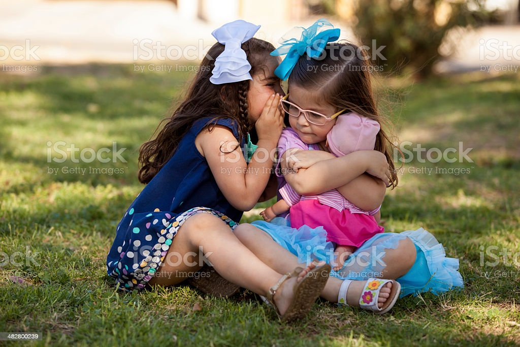 Little brunette telling a secret stock photo