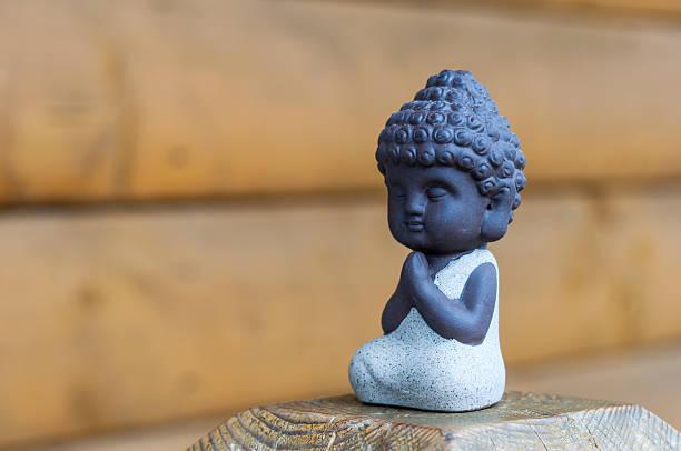 little buddha beten oder meditieren auf einem hölzernen hintergrund mit leeren - achtsamkeit persönlichkeitseigenschaft stock-fotos und bilder