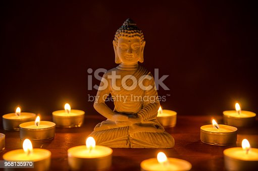 little buddha statue surrounded by tea candles