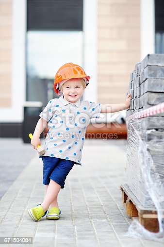 istock Little builder in hardhats with hammer working outdoors 671504084