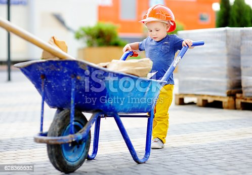 527687520 istock photo Little builder in hardhats with wheelbarrow working outdoors 628365532