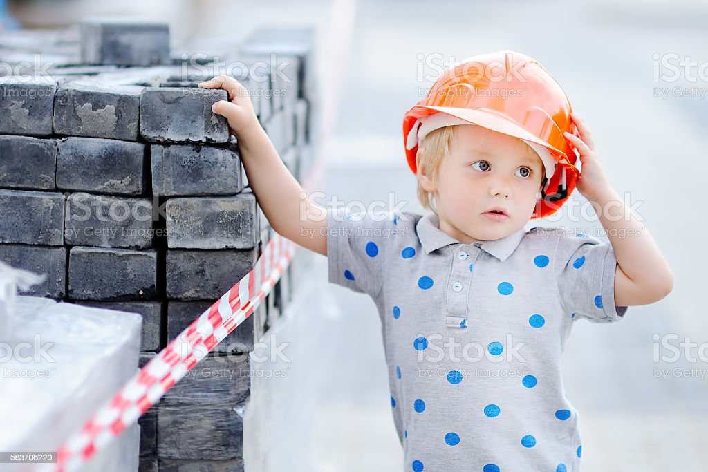 Little builder in hardhats working outdoors stock photo