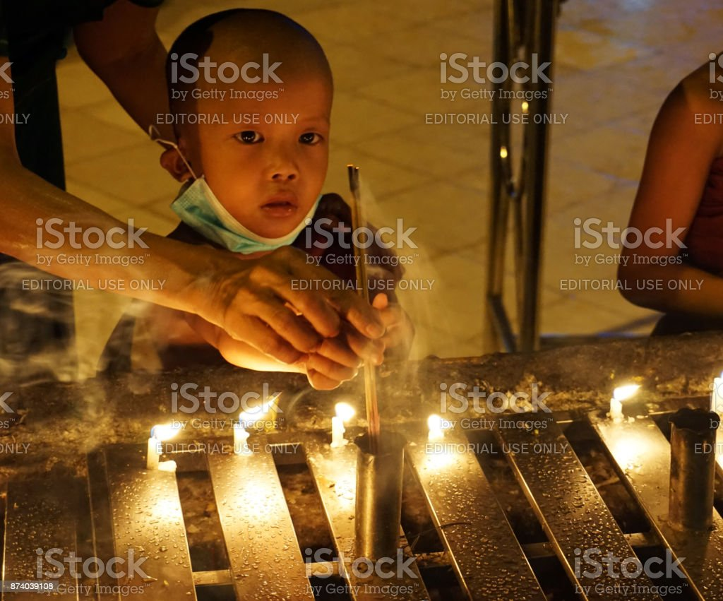Little Burmese monk with traditional dolls stock photo