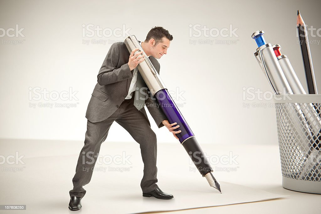 Little business man sign with giant pen at work royalty-free stock photo
