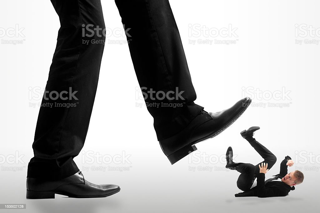 Little businessman being crushed by the feet of giant businessmen stock photo