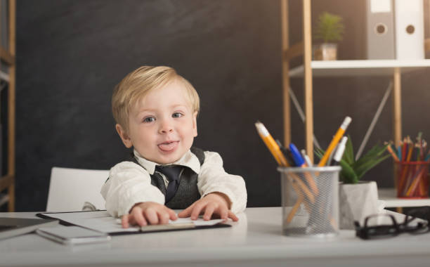 Little businessman having fun at office stock photo