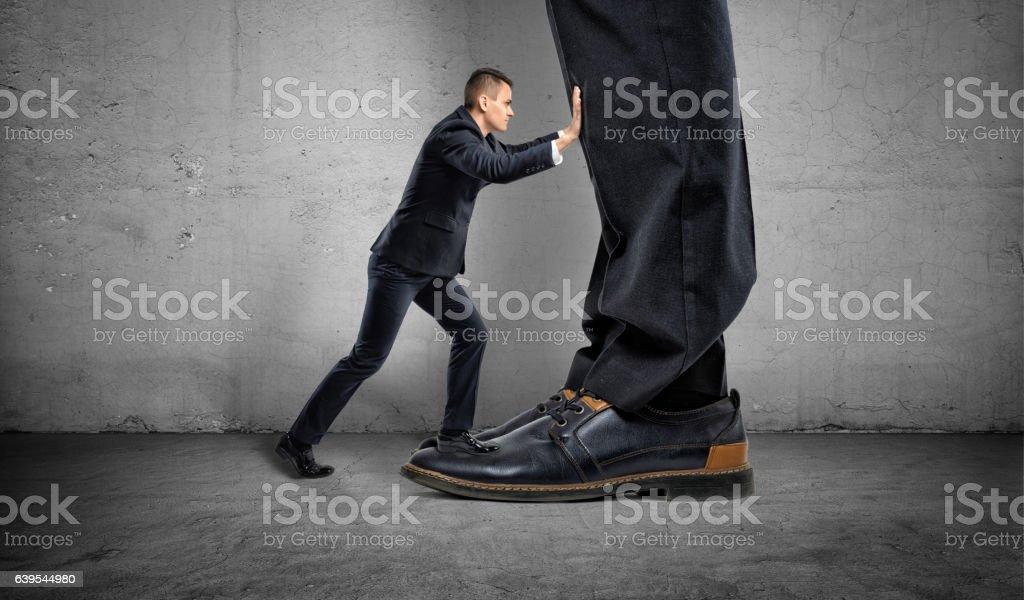 Little businessman is pushing a big boss's huge feet stock photo