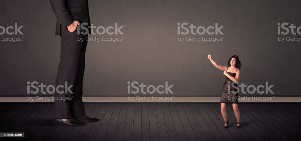 Little bussineswoman in front of a giant boss legs concept stock photo
