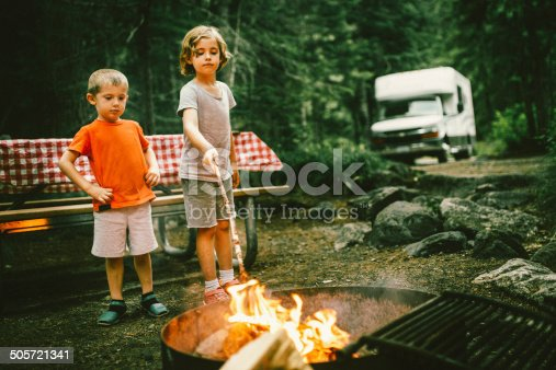 Little campers on motorhome road trip preparing a campfire.