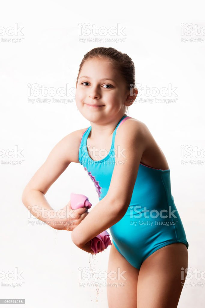 0b8fde66721 Little caucasian 7 years old cute caucasian girlie in cyan swimming costume  twistting a pink shammy - Stock image .