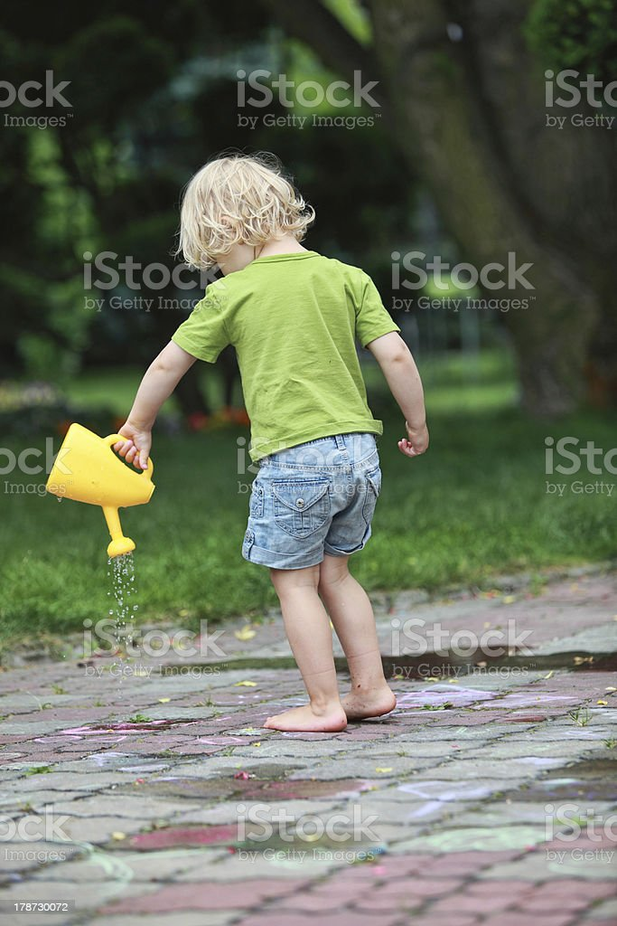 Little caucasian barefoot girl playing with watering can royalty-free stock photo