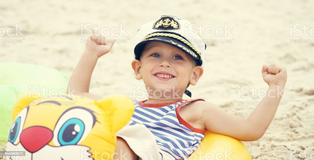 ca554dedf Little Caucasian Boy In Sailor Suit And Cap Sitting On The Beach In ...
