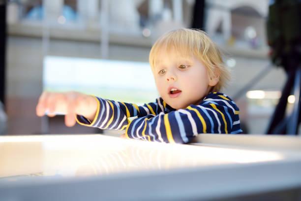 Little caucasian boy is looking at an illuminated info panel. stock photo
