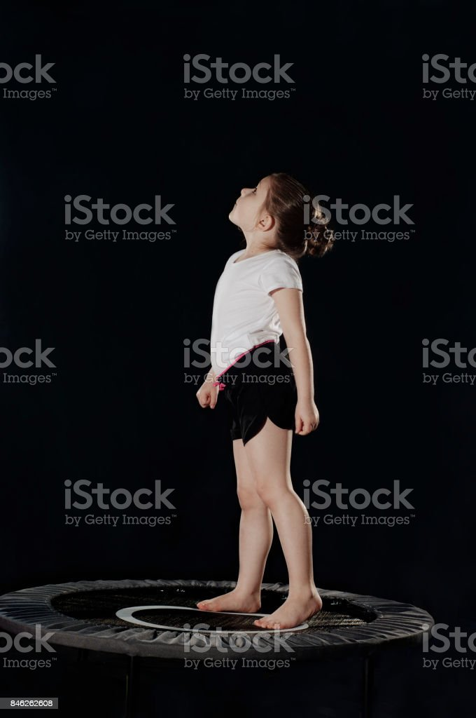 Little caucasian female gymnast staing on trampoline and watching up. stock photo