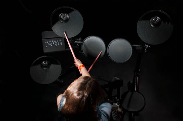 petit batteur caucasien fille jouer le kit de batterie elettronic - batterie musique photos et images de collection