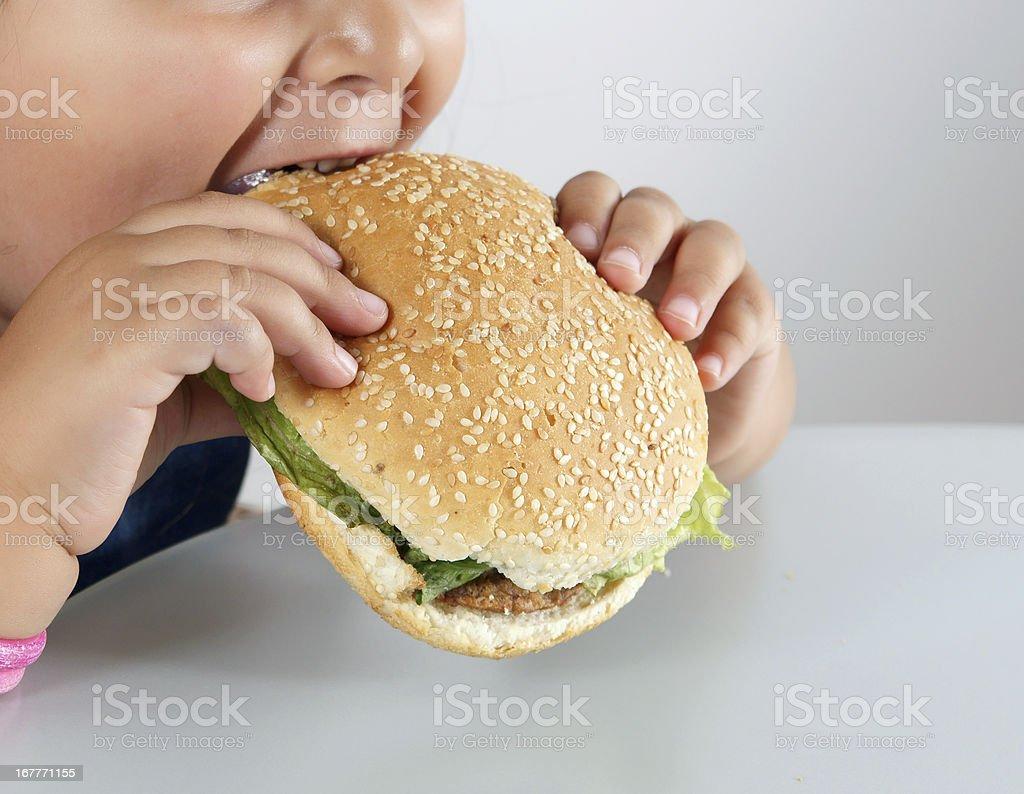 little caucasian girl eating burger stock photo